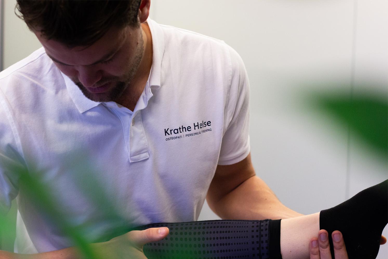 Osteopat Marius Krathe behandler pasient, nærbilde av skjorte med logo på