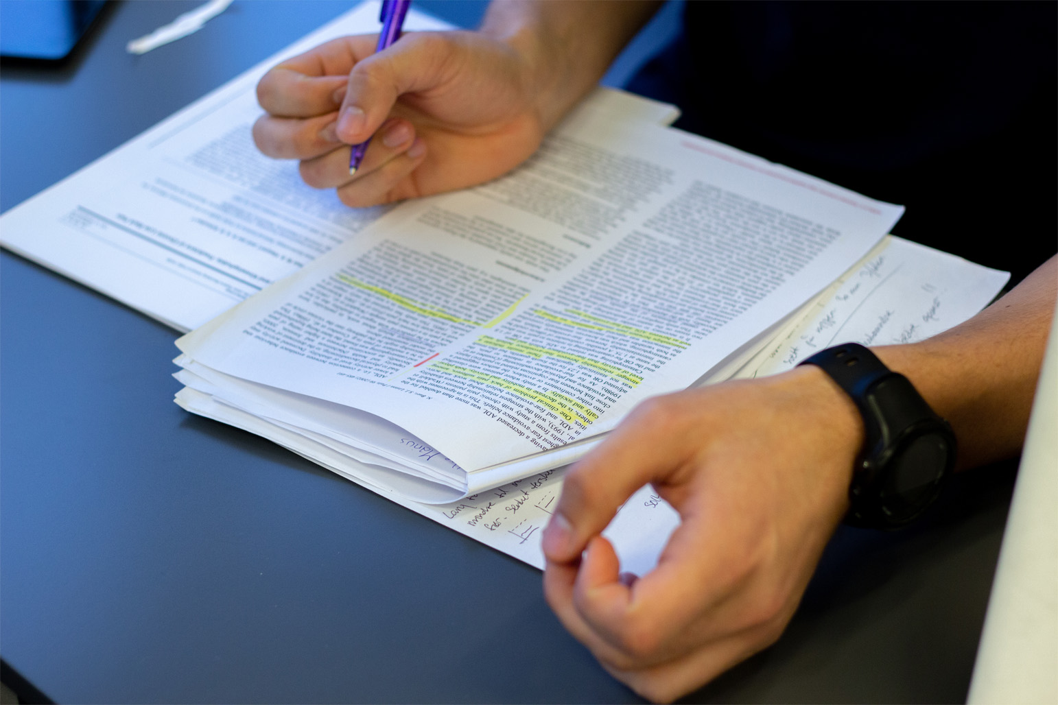 Mann som holder penn og skriver notater i et dokument med tekst