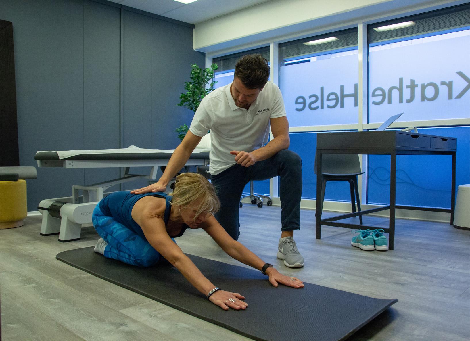 Osteopat Marius Krathe veileder en pasient som gjør øvelser på en matte